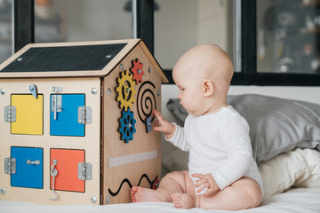 A child is playing with a wooden house. A special model of a house with many functions for the development of fine motor skills. Busy Board.