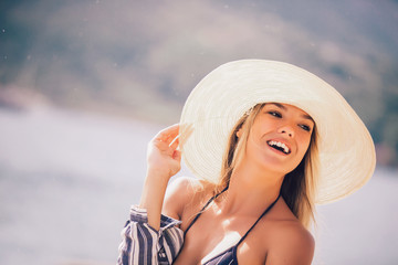 Beautiful girl in a white hat smiling at the summer waterfront
