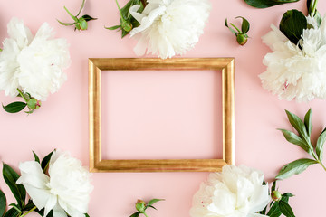 Gold frame decorated of white peony flowers on pink background. Peony texture. Flat lay, top view.