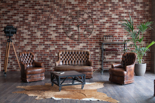 Loft interior photo. Red brick wall with big clock, table, leather chair and coach and vintage light source lamp and palm tree in a pott.