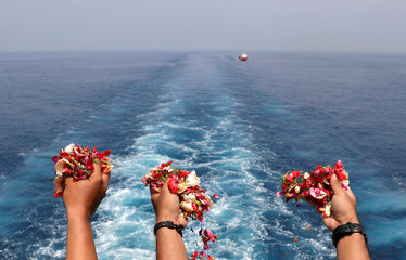 Families and colleagues of passengers and crew of Lion Air flight JT610 throw flowers and petals from the deck of Indonesia Navy ship KRI Banjarmasin as they visit the site of the crash to pay their tribute, at the north coast of Karawang
