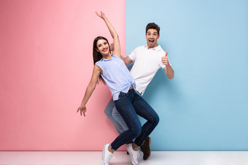 Full length image of optimistic man and woman in casual wear laughing and having fun together, isolated over colorful background