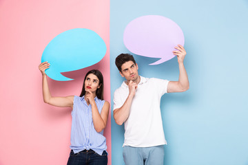 Image of young man and woman holding copyspace bubbles for advertisement, isolated over colorful background