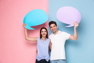 Image of optimistic couple holding copyspace commercial bubbles for text, isolated over colorful background
