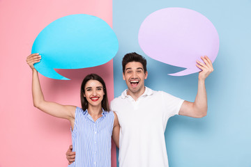 Image of joyous man and woman holding blank bubbles for announcement, isolated over colorful background