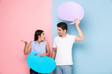 Image of excited man and woman holding copyspace posters for announcement, isolated over colorful background