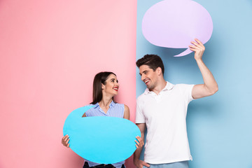 Image of smiling couple holding copyspace bubbles for announcement, isolated over colorful background