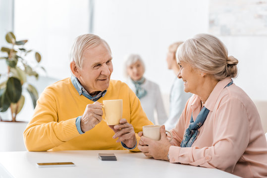 smiling senior man and woman drinking tea at table in clinic