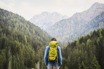 Young backpacking man traveler enjoying nature in Alps mountains. Travel and active lifestyle concept.