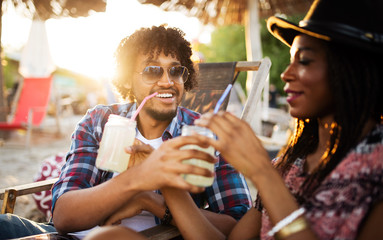 Young happy black couple with drinks relaxing on the beach
