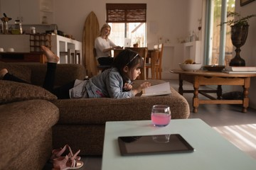 Girl reading a book in living room
