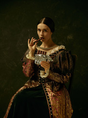 Portrait of a girl wearing a princess or countess dress over dark studio. portrait with sweet chocolate bar over dark studio
