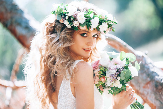 beautiful bride in nature in a coniferous forest in a wreath on her head and a luxurious wedding dress