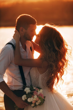 bride and groom kiss at sunset. wedding concept in nature at sunset.