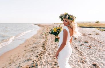 beautiful bride walks near the sea