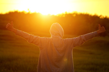 a man in the light of the sunset with his hands up, the concept of success, freedom and joy