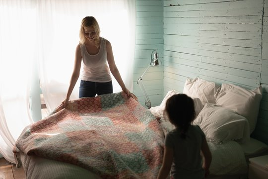 Mother and daughter placing blanket on bed in bedroom