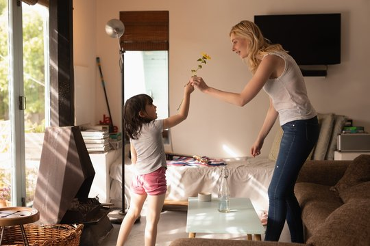 Daughter giving flower to her mother in living room