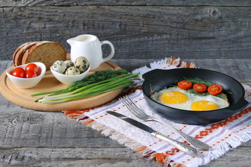 Breakfast on the table. Fried chicken eggs and fresh vegetables.