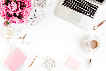 Flat lay women's office desk. Female workspace with laptop, pink peonies bouquet, accessories on white background. Top view feminine background.