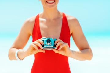 Closeup on woman taking photos with retro photo camera on beach