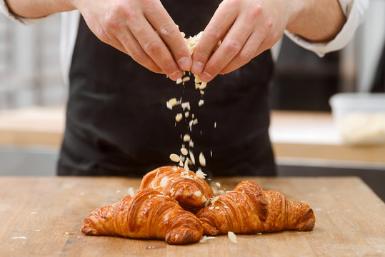 Baker sprinkles croissants with almond
