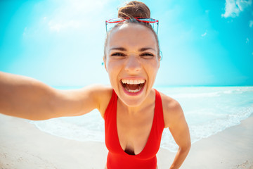 smiling young woman in red swimsuit on seashore taking selfie