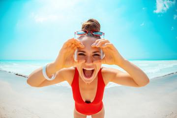 woman on seashore looking through binocular shaped hands