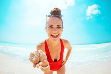 happy modern woman in red swimwear on beach showing sea shell