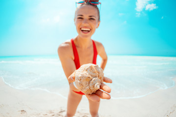 Closeup on smiling young woman on seacoast showing sea shell