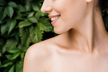 smile of young beautiful woman with green leaves at background