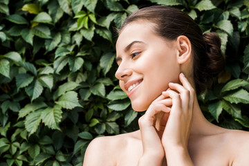 smiling young woman with hands near face on green leaves background