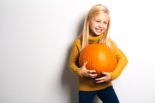 A Cute girl 5 year old posing in studio with pumpkin
