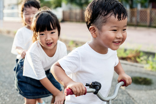 Smiling friends playing on street with bicycle