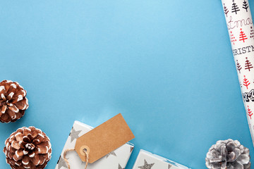 A blue Christmas card with copy space, cones, presents and wrapping paper