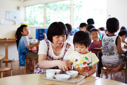 Female teacher sitting at table in a Japanese preschool, helping young boy to eat his lunch.