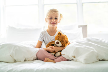 A Cheerful little girl in bed having fun