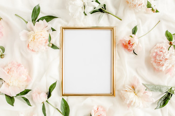 Gold frame decorated of beautiful beige peonies. Flat lay, top view. Valentine's background. Floral frame. Peony texture.