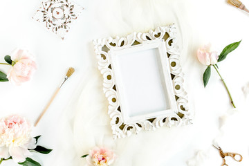 Carved, white frame decorated of white peony flowers, accessories on white background. Flat lay, top view.