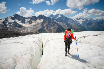 Female mountaineer enjoying the beauty of the glacier walks on the glacier in the crampon and sunglasses. Against the backdrop of the high mountains of the Caucasus sky and clouds