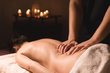 Close-up of male hands. Masseur does massage for the waist of a young girl. Rehabilitation, beauty therapy medicine. healthy concept