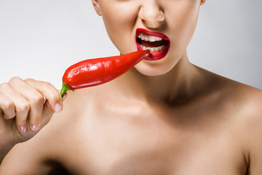close up of young beautiful woman with red lips biting chili pepper