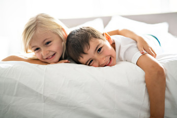A Portrait of happy siblings lying under blanket on bed in bedroom at home