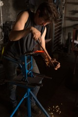 Female metalsmith shaping horseshoe in factory