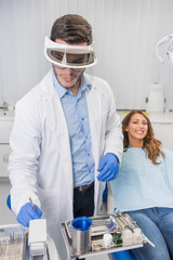 Male dentist wearing surgical mask and safety glasses