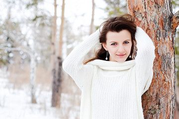 portrait of a girl with dark hair and a white jacket on the background of a snow Park