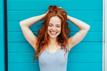 Smiling happy woman running hands through hair