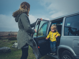 Mother helping toddler get out of car on the moor
