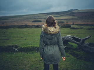 Young woman by fallen tree on the moor