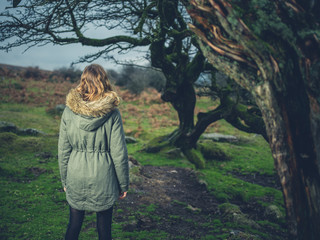 Woman standing by tree on the moor